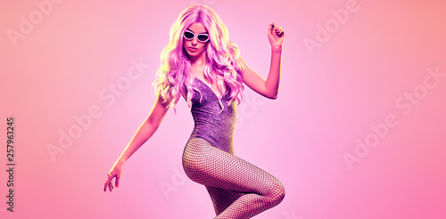 Disco Party Doll girl with pink neon hairstyle dance. High Fashion. Young Gorgeous woman in Colorful uv Light. Music vibes. Pop Art fashionable Style. Night Club, dancing neon concept