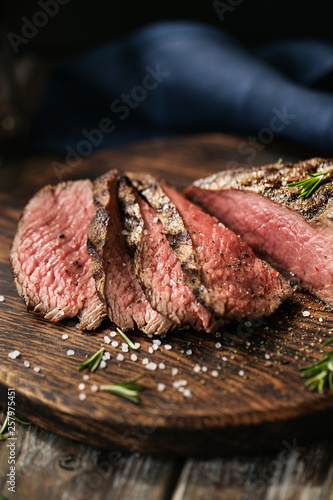 Juicy medium Beef Rib Eye steak slices on wooden board with herbs spices and salt. - 257975451