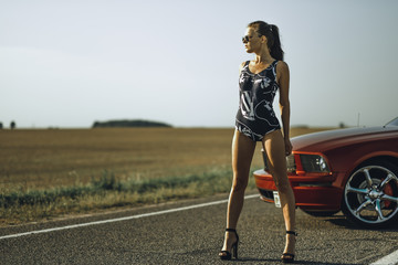 beautiful girl in bodysuit wearing sunglasses near red sports car