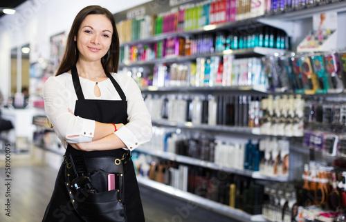 Leinwandbild Motiv Professional positive female hairdresser standing in shop