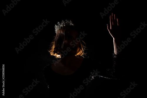 Portrait Silhouette Shadow Back Rim Light of Miss Pageant Beauty Queen Contest Silver Diamond Crown wave hand express feeling smile, studio lighting dark black background, turn front face to camera