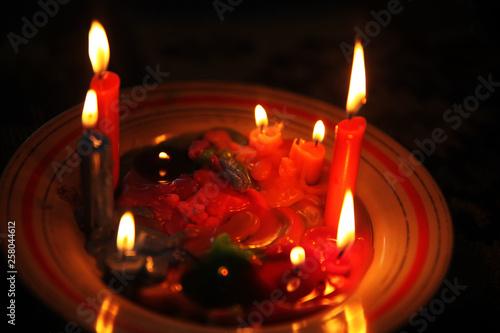 Colored candles burning in the dark © ALYEVA