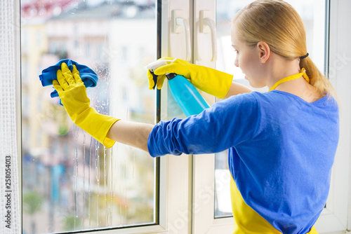 Woman cleaning window at home © Voyagerix