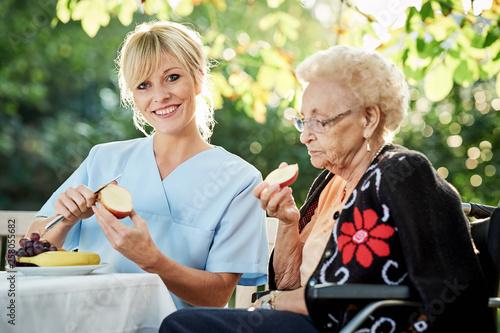 Pflegerin hilft Seniorin beim schälen von Obst © Karin & Uwe Annas