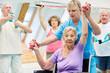Leinwandbild Motiv Alte Frau trainiert mit Hanteln im Reha Kurs