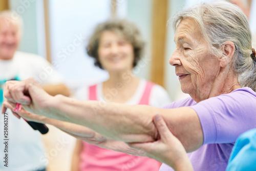 Leinwanddruck Bild Seniorin bei Übung mit Elastikband