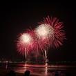 Leinwandbild Motiv Amazing beautiful colorful fireworks display on celebration night, showing on the sea beach with multi color of reflection on water