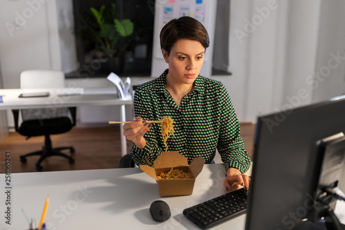 business, deadline and people concept - businesswoman eating takeaway wok food by chopsticks and working on computer at night office - 258065243