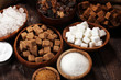Various types of sugar, brown sugar and white on rustic wooden table