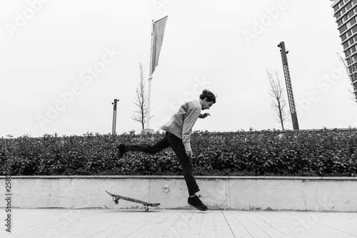 fototapeta na ścianę Black and white image of young man showing skills with skateboard