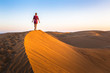 Leinwanddruck Bild - Girl walking on sand dunes in arid desert at sunset and wearing dress, scenic landscape of Sahara or Middle East