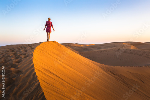 Leinwanddruck Bild Girl walking on sand dunes in arid desert at sunset and wearing dress, scenic landscape of Sahara or Middle East