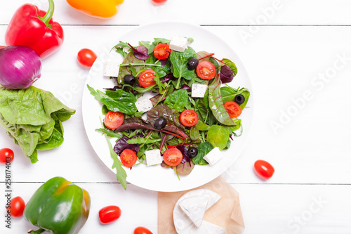 Salad in a white plate, cheese and vegetables on a white wooden background - 258174013
