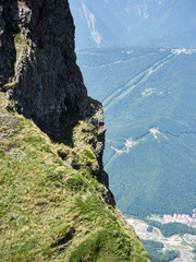 The rock on a high mountain slope, in front of which is a valley with residential houses. © Дмитрий Поташкин