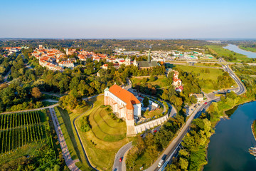 Sandomierz, Poland. Medieval gothic castle in front, old town with town hall tower, gothic cathedral and Vistula river in the background. Aerial view in sunset light