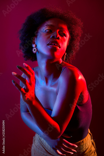 African woman dancing in neon light on a pink background. Glamorous portrait of a black woman. - 258250494