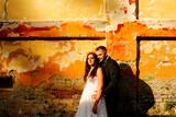 Beautiful wedding couple posing outdoor near old wall