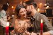 Leinwandbild Motiv Young man kissing his fiance on a night out