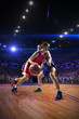 Basketball player n action. around Arena with blue light spot