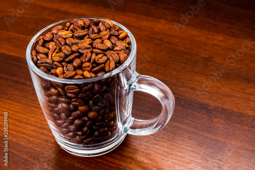 Roasted coffee beans in a glass cup isolated on a rustic dark wood table background © Alvis