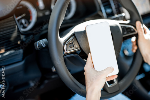 Woman holding a smart phone with empty screen to copy paste while driving a car on the steering wheel - 258294221