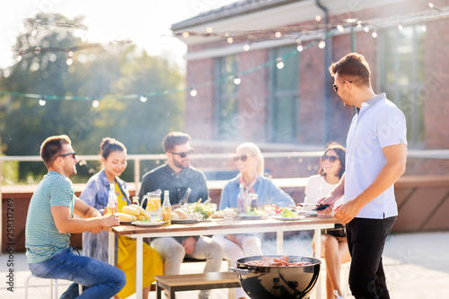 leisure and people concept - happy man grilling meat on bbq and friends at rooftop party - 258317269