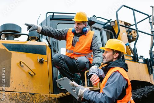 Leinwanddruck Bild Vorarbeiter gibt Arbeiter im Tagebau Tipps und Anweisungen