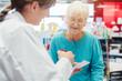 Leinwanddruck Bild - Ältere Frau in der Apotheke unterhält sich mit der Apothekerin