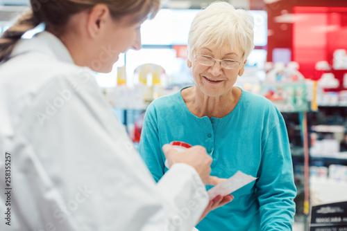 Leinwanddruck Bild Ältere Frau in der Apotheke unterhält sich mit der Apothekerin
