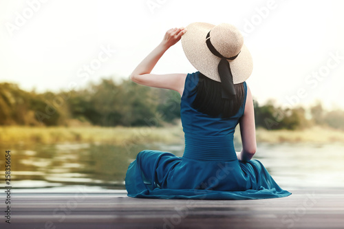 Unplugged Life and Relaxation Concept. Portrait of Young Woman Relaxing by Riverside. Sitting on Wooden Deck and Looking away © blacksalmon