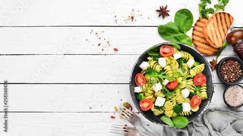 Pasta with spinach, tomatoes and feta cheese. In a black plate on a wooden background Top view. Free space for your text. Flat lay © Yaruniv-Studio