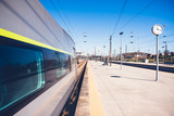Beautiful railway station with modern commuter train at sunny day. Railroad outdoor platform