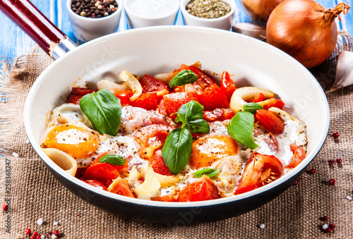 Shakshuka - fried eggs with vegetables in frying pan - 258368247