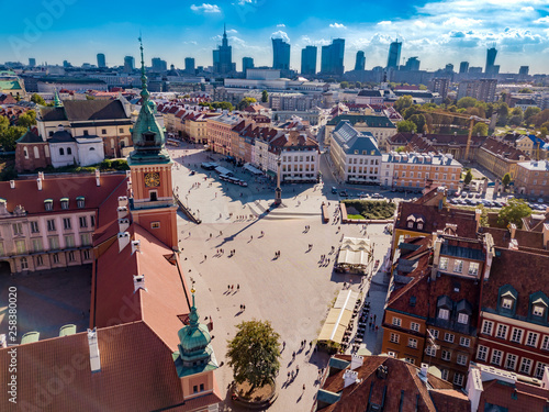 Royal Castle at central square of polish capital - Warsaw. many tourists visit this town in sunny day. There are many historic, old buildings surrounding square and castle. Aerial