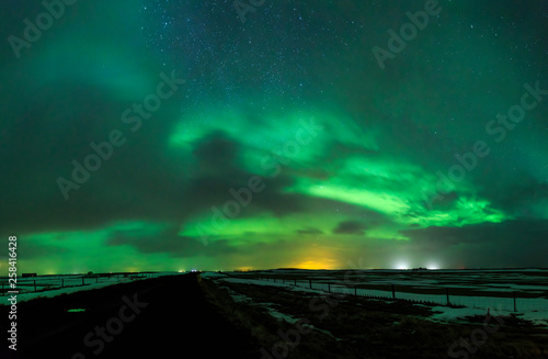 Leinwandbild Motiv Northern lights Aurora Borealis above a road