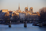 Paris, France - February 24, 2019: Notre Dame cathedral and Arts bridge at sunset in Paris
