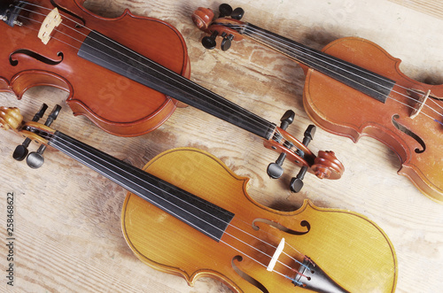 Three violins on a wooden table - 258468622