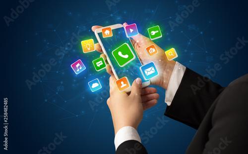 Leinwandbild Motiv Female hand using smartphone with 3D shiny starlike application icons around