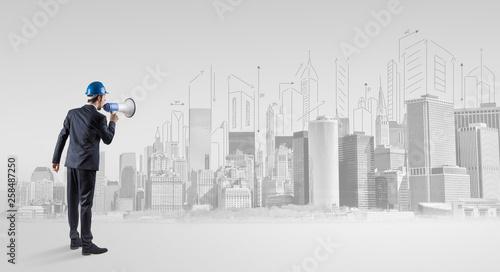Leinwandbild Motiv Young supervisor architect standing and replanning a big city panorama