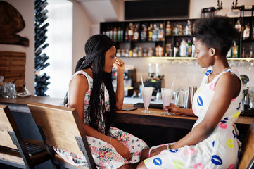 Two black african girlfriends at summer dresses drinking milkshake cocktails in bar.