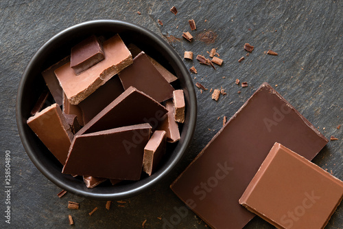 Pieces of dark and milk chocolate in black ceramic bowl isolated on grey slate from above. Small bits of chocolate.
