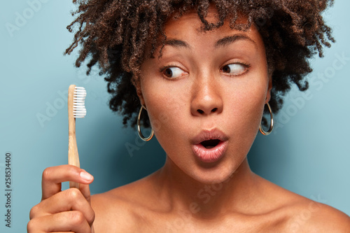 Leinwandbild Motiv Close up shot of shocked beautiful woman looks at wooden toothbrush, wonders brilliant effect of toothpaste, opens mouth from surprisement, leads healthy lifestyle. Morning time and daily habits