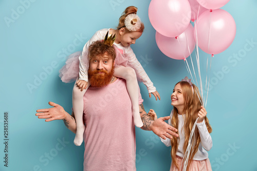 Leinwandbild Motiv How to celebrate? Uncertain bearded man with ginger beard gestures doubtfully, plays with two small kids, celebrate holiday. Playful naughty girl on fathers shoulders stretches hand to sister