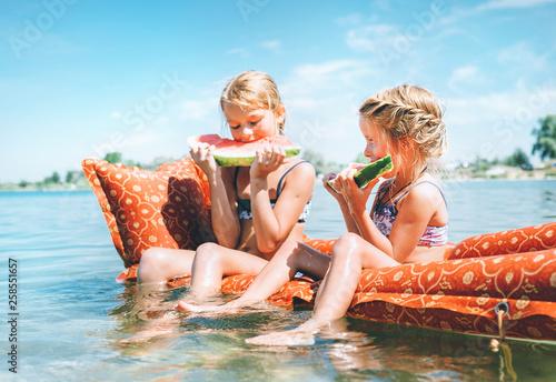 Leinwandbild Motiv Two little sisters sitting on innflatable mattrace and eating watermelon