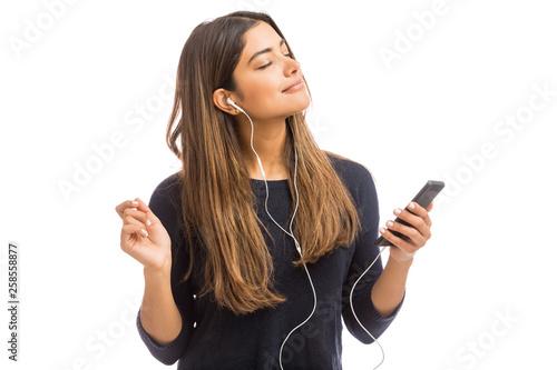 Woman Using Radio To Listen Music On Smartphone - 258558877