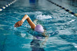 Leinwandbild Motiv Female athlete swimming fast in crawl style.  Splashes of water scatter in different directions.