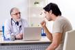 Leinwandbild Motiv Young man visiting old male doctor