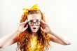 Surprised curly redhead girl in glasses with a yellow bow on her head wearing yellow t-shirt looking to the camera with schoked emotion