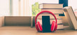 A black mobile phone  wearing red headphone learning book pile on wooden table. - 258588439