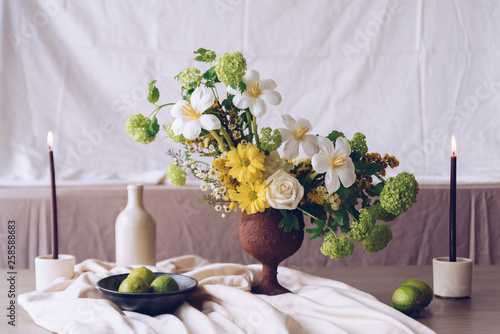 Still life with a beautiful bouquet of flowers, candles and limes © SianStock